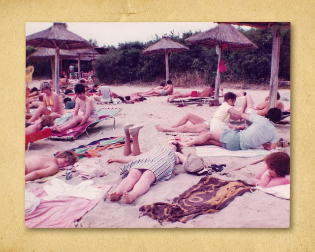 Photograph of a colour photographic print, resting on a brown paper textured background. The print shows a beach scene with many people lying on towels and sun beds enjoying the sun. In the background are parasols made of wooden poles and dried grass umbrellas. In the middle of the scene are a pair of prosthetic legs sticking out from the sand, upside down, feet in the air, disappearing into the sand at the knees.