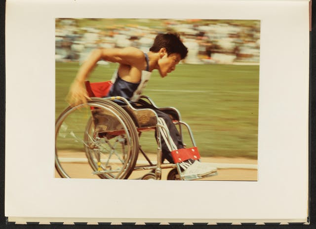 Photograph of a colour photographic print showing a man in a wheelchair competing in a Paralympic event. He is dressed in athletic clothes with a competitor number pinned to his front and back. His arms are raised behind him, caught mid action as he propels his wheelchair forwards. He has an expression of determination on his face. The background of the image and his arm are blurred in motion which gives the image an active, dynamic feeling.