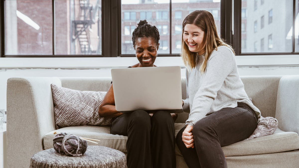 Two women on sofa with laptop