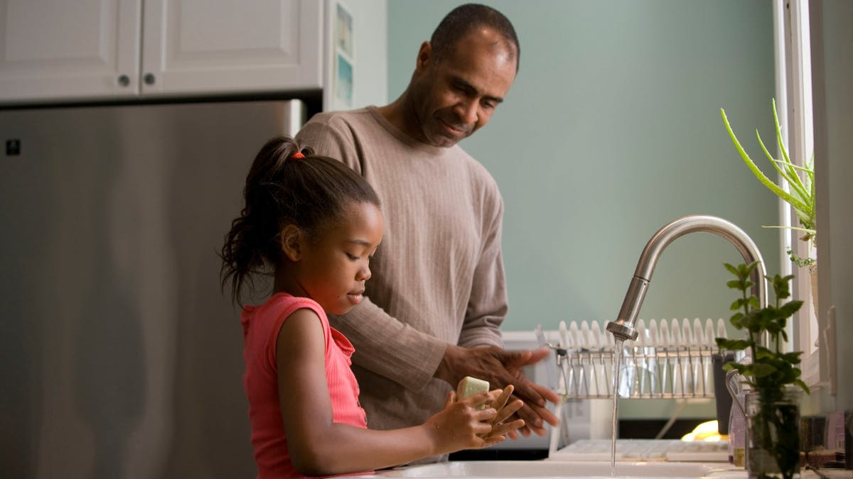 Man and child washing hands