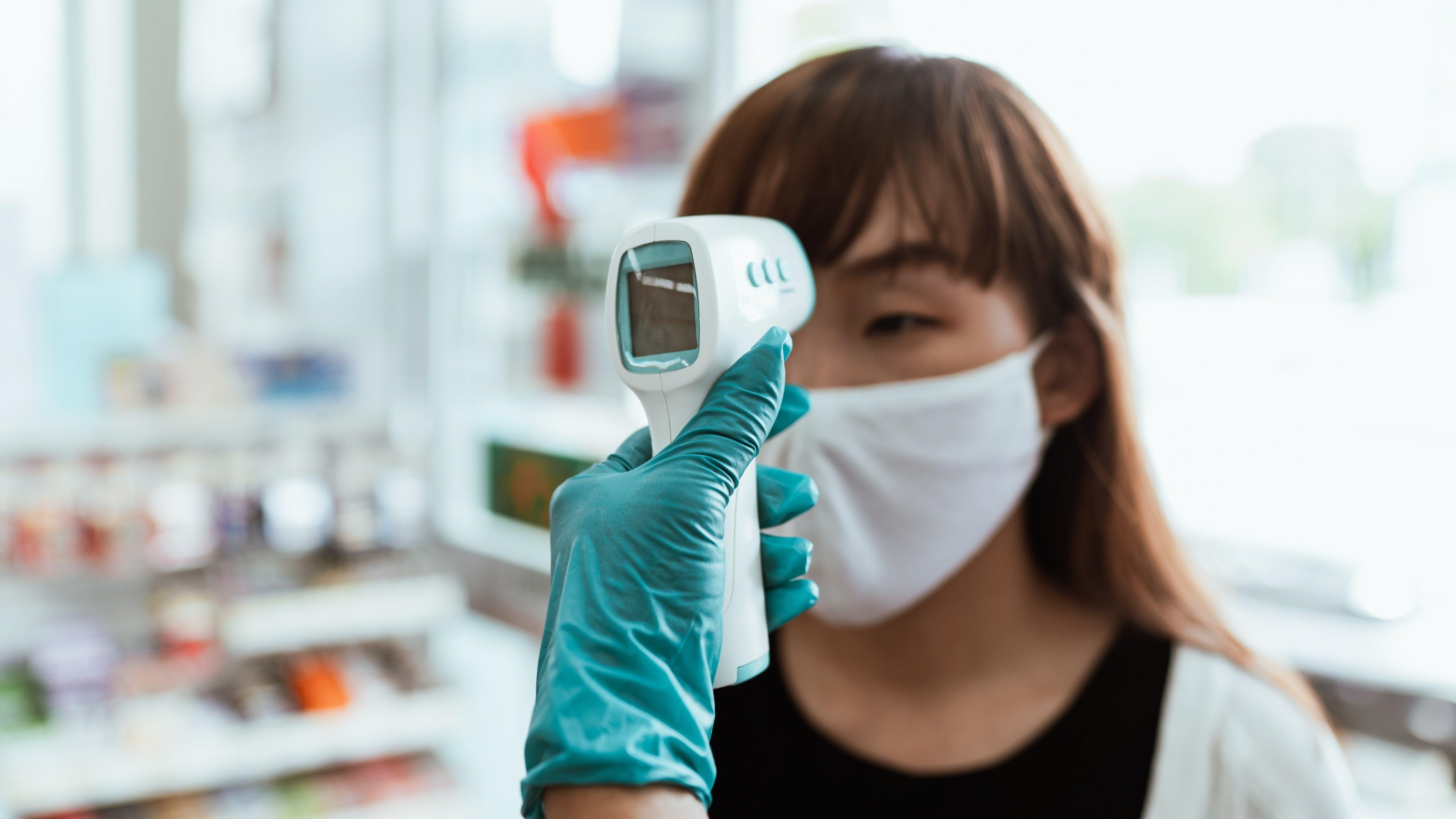Woman having temperature checked