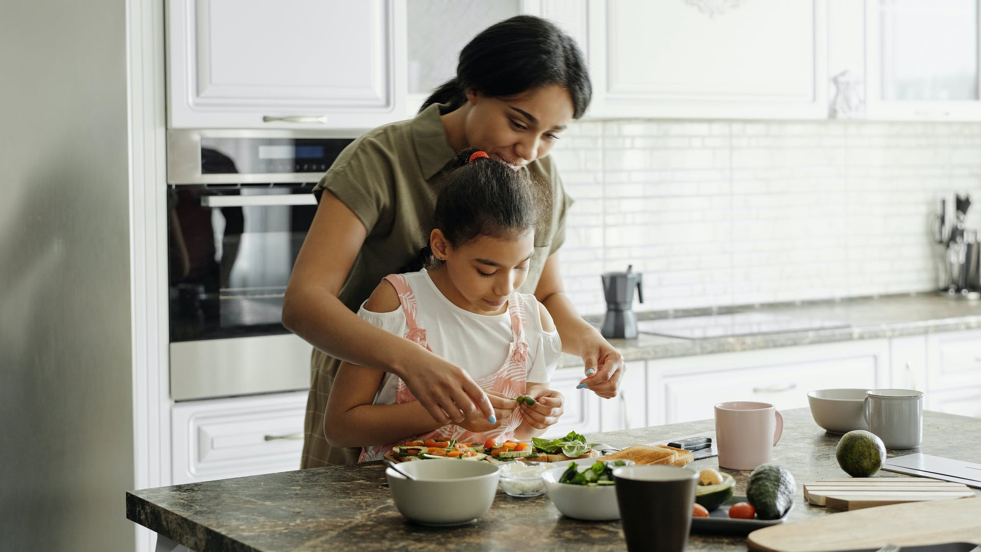 A woman and child preparing food together.
