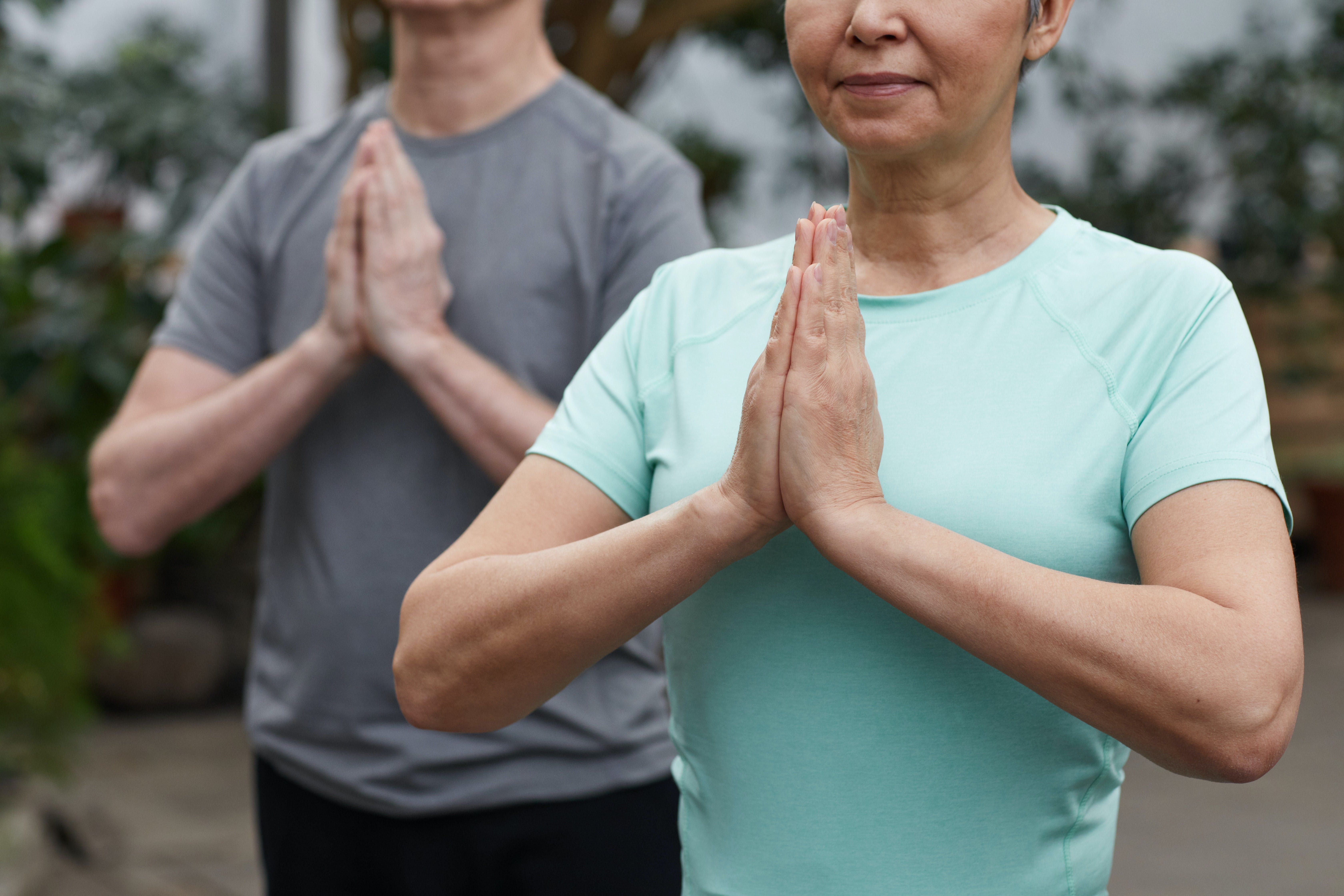 A mand and woman stand in the namaste yoga pose.