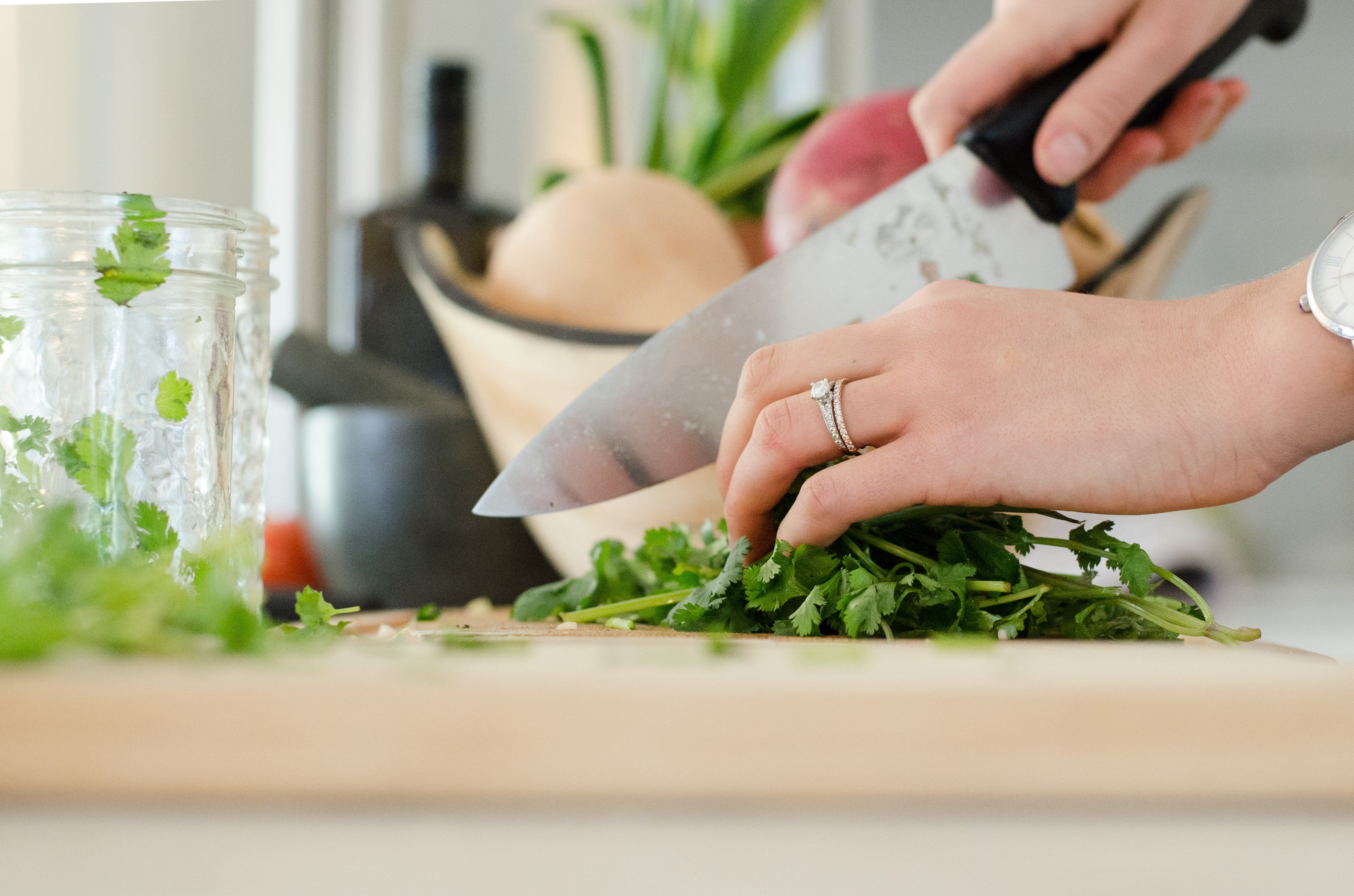 A close up photo of someone's hands as they chop up coriander.