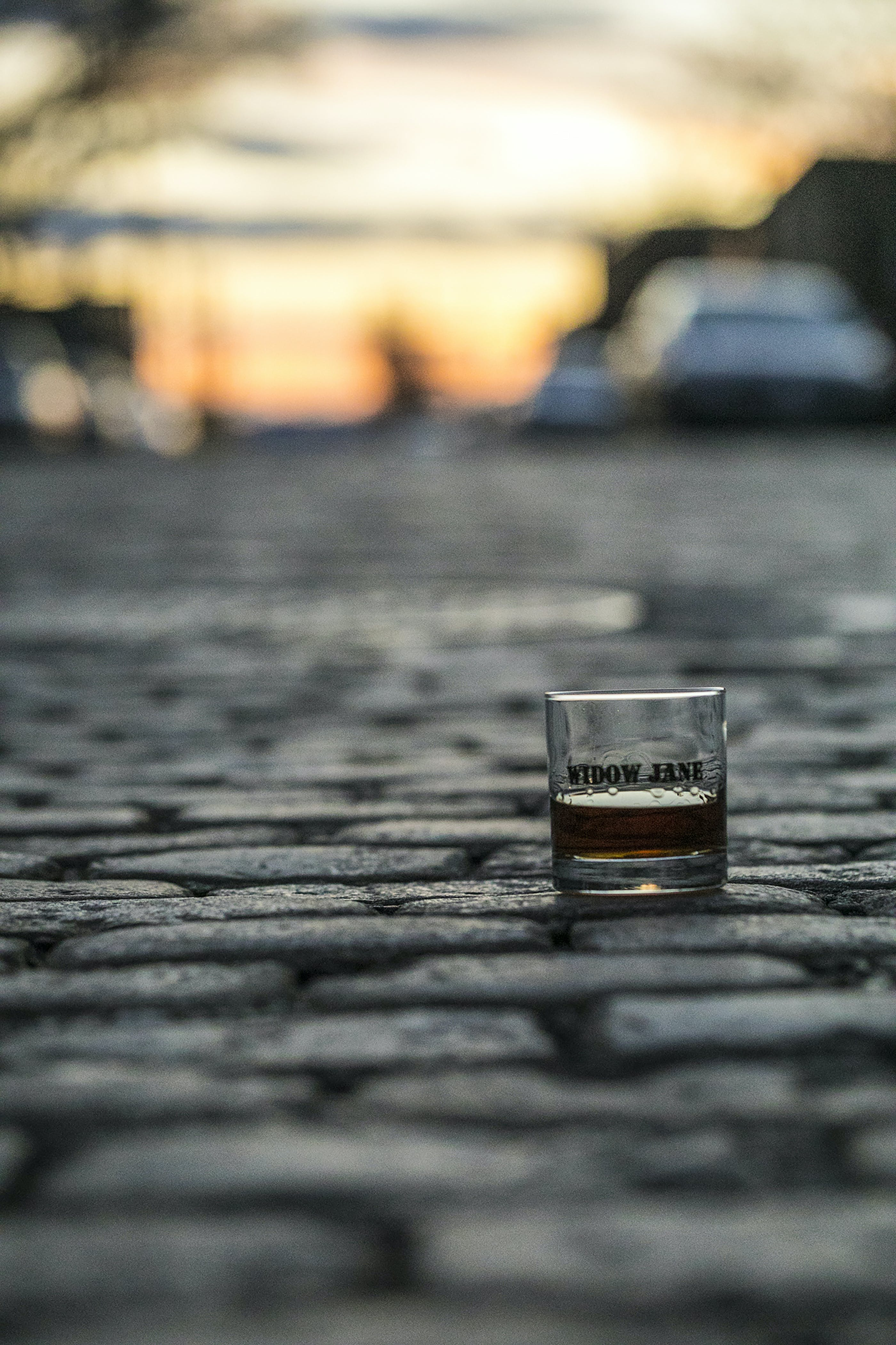 A glass of whiskey on a cobblestone street