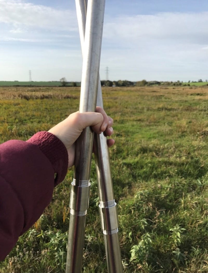 A hand holding two metal poles in front of a grassy field