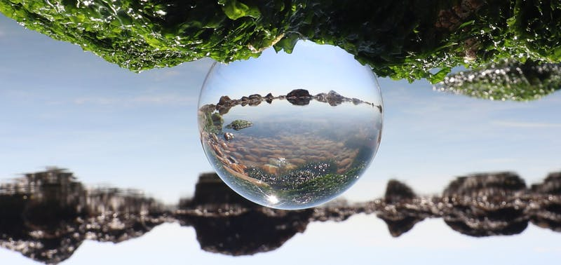 A water droplet showing a rocky landscape