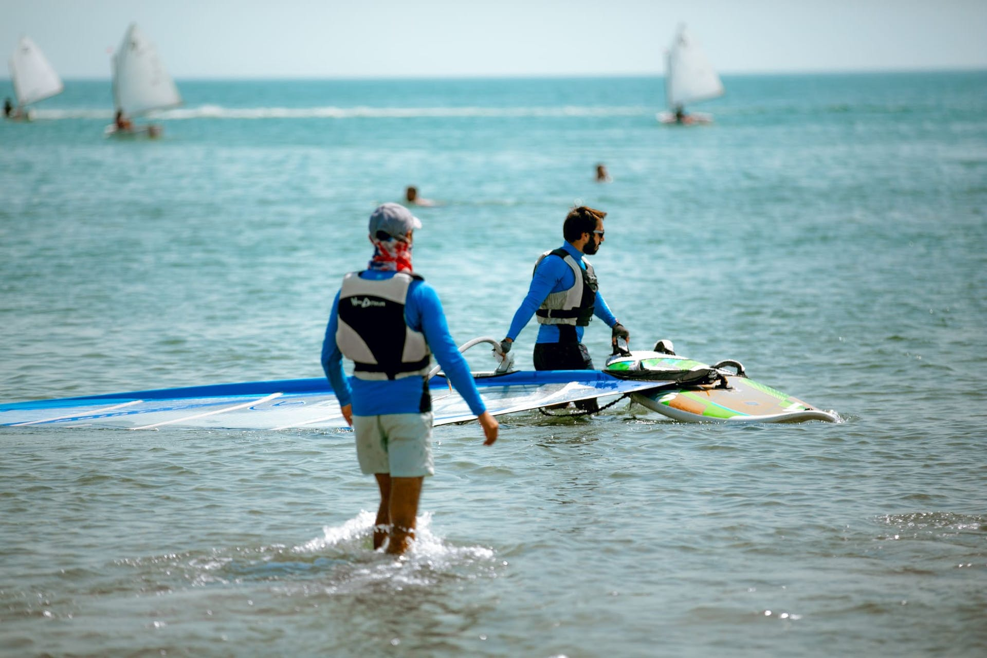 Windsurfing team members on a shore