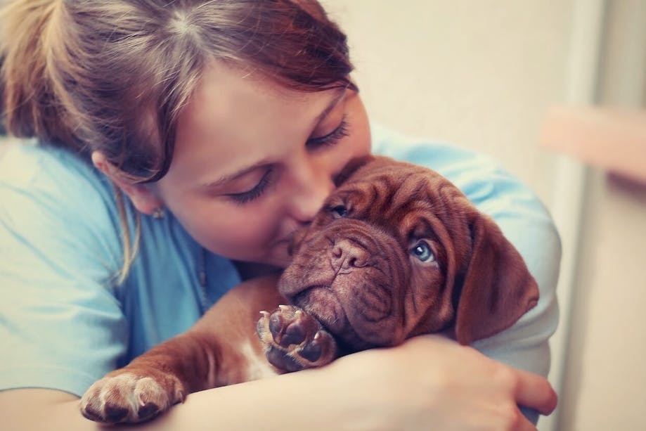 Woman hugging and kissing her puppy