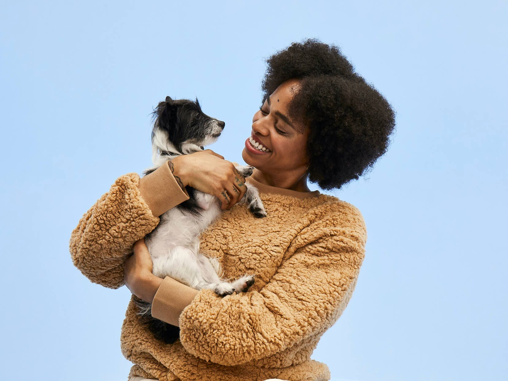 Woman cuddling her dog before a DNA test
