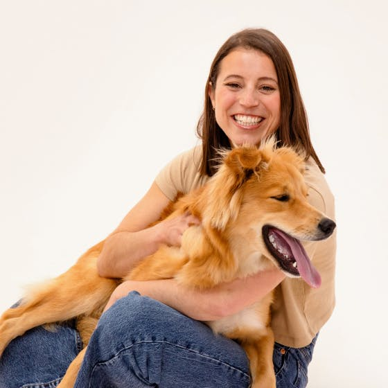 Woman smiling while holding her dog