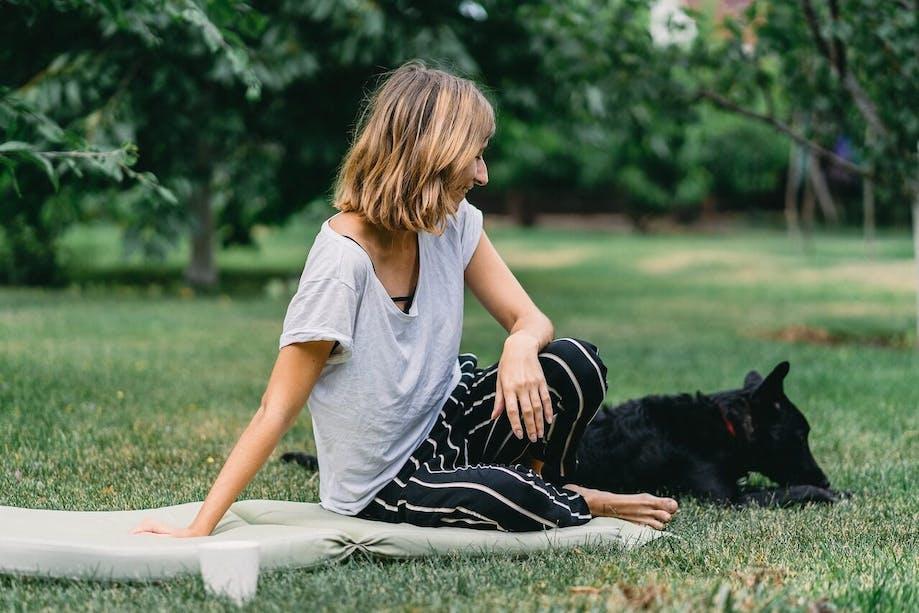 Woman sitting on blanket outside beside her black dog