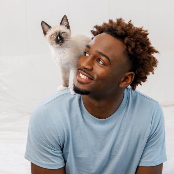 Man smiling while looking up at his kitten