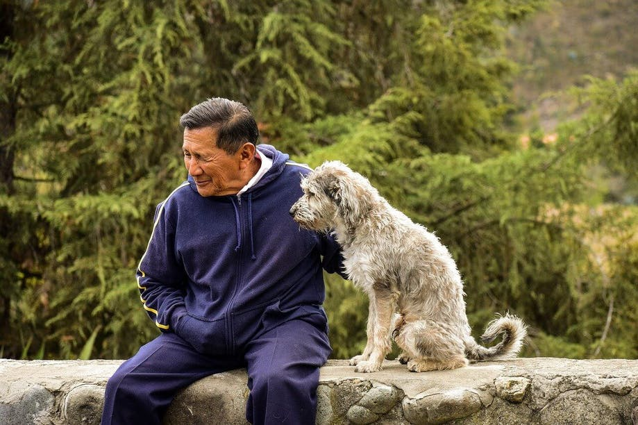 Elderly man sitting next to his dog