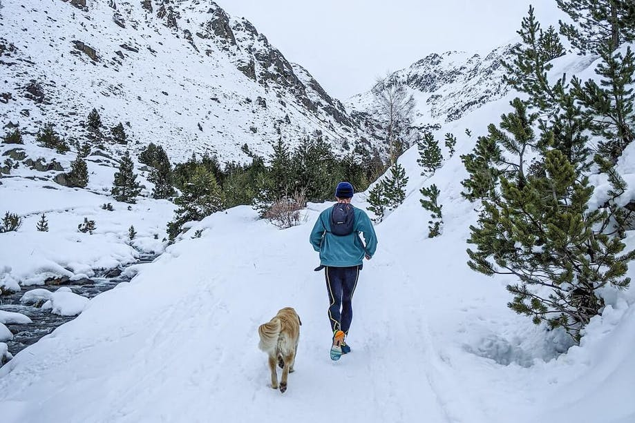 Man running in the winter weather with his dog