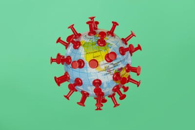 A toy globe is modeled to look like a virus cell under the microscope. It is shot on a green background and shows North America. It illustrates the concept of the pandemic affecting all areas of the globe.
