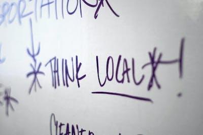 """Think local!"" written on a whiteboard in dark ink."
