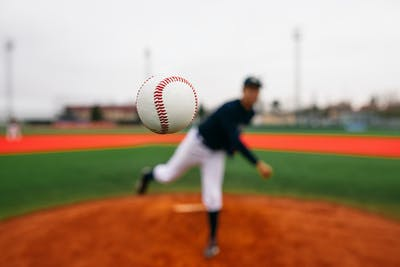 White baseball flying directly toward camera after powerful throw from blurred pitcher during baseball match on field