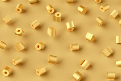 Pattern from flying rolls of golden painted toilet paper on a gold background with soft shadow.
