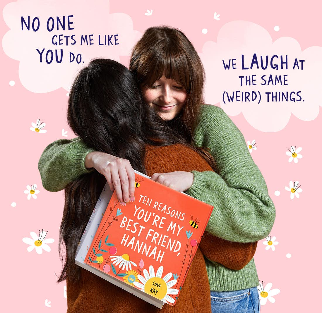 Two friends hugging whilst holding Ten Reasons You're My Best Friend
