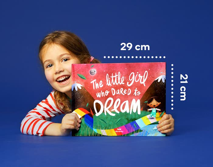 Child holding Dared to Dream book showing dimensions 29cm length by 21 cm height