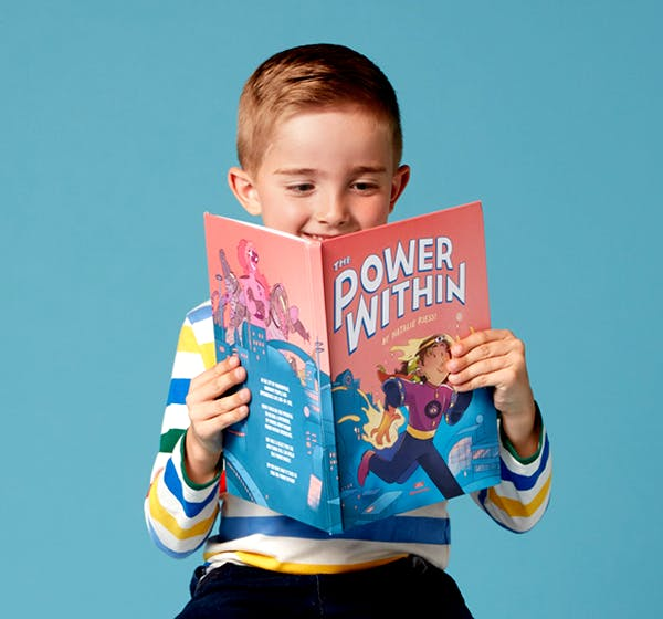 A child reading The Power within and smiling