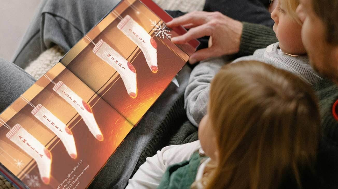 A father reading The Christmas Snowflake book for son and daughter