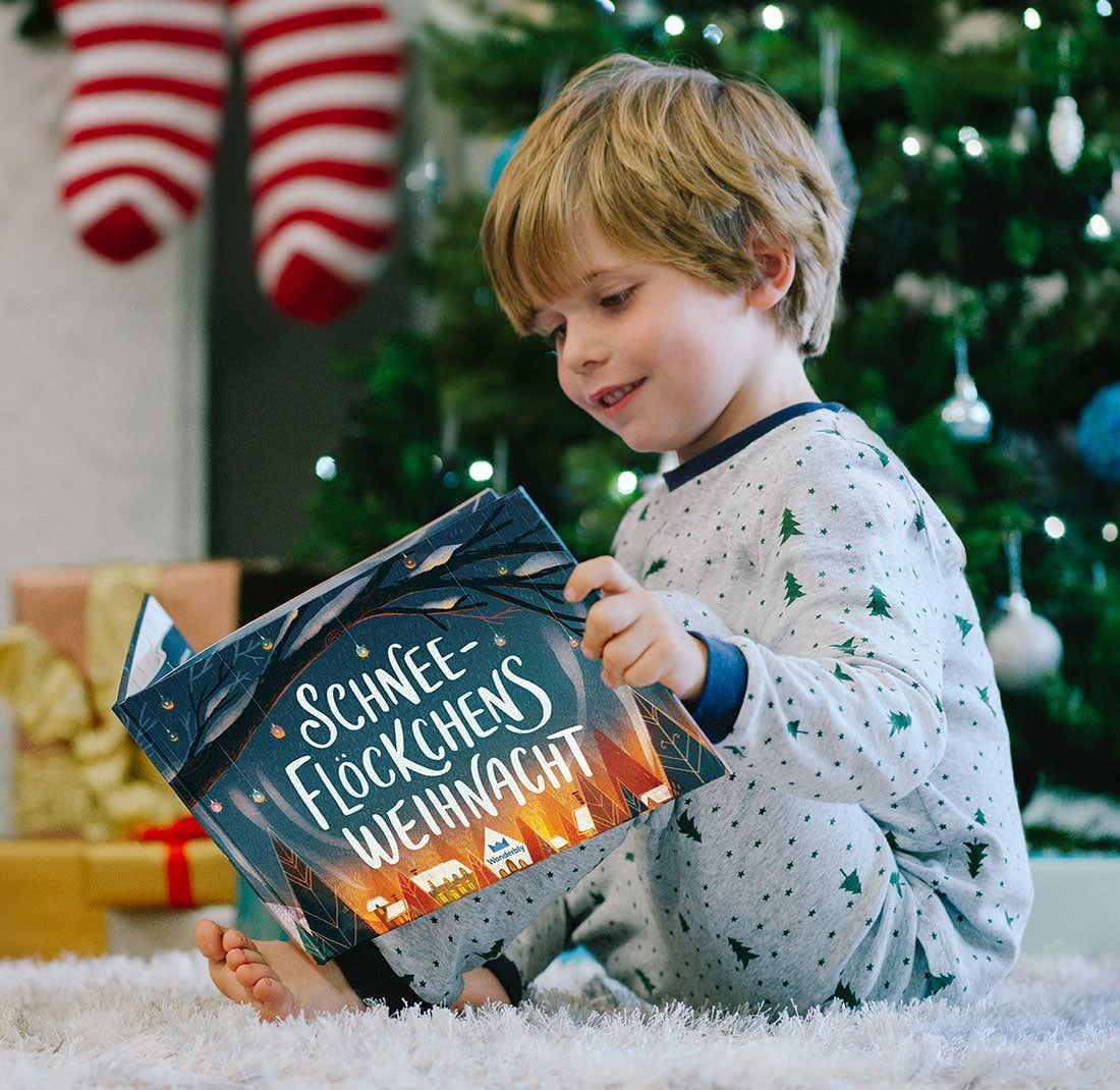Kind liest Schneeflöckchens Weihnacht und lächelt