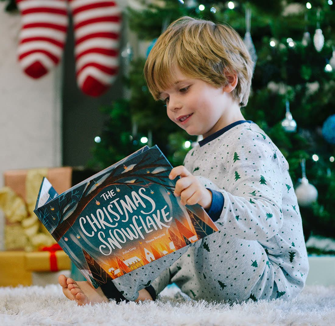Little boy reading The Christmas Snowflake