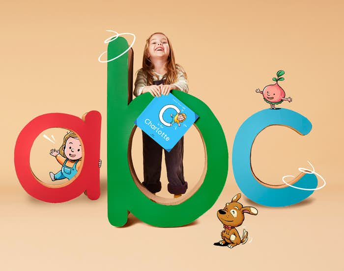A little girl holding her personalized copy of ABC for You