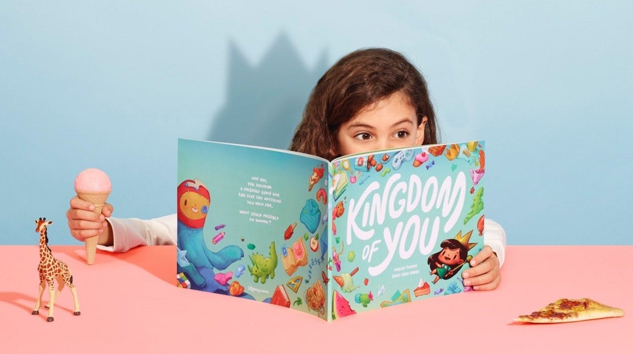 A little girl holding an ice cream as she reads the Kingdom of You book