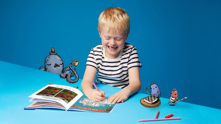 Little boy using the Wonderbly Coloring and Activity Book