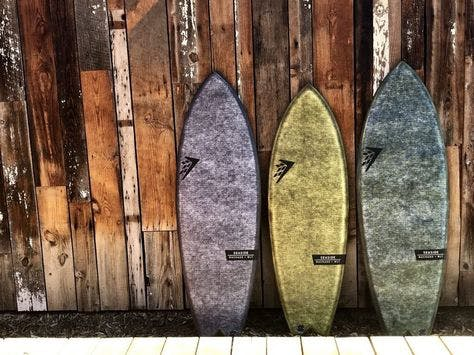 Three seaside boards lined up against a wooden wall.