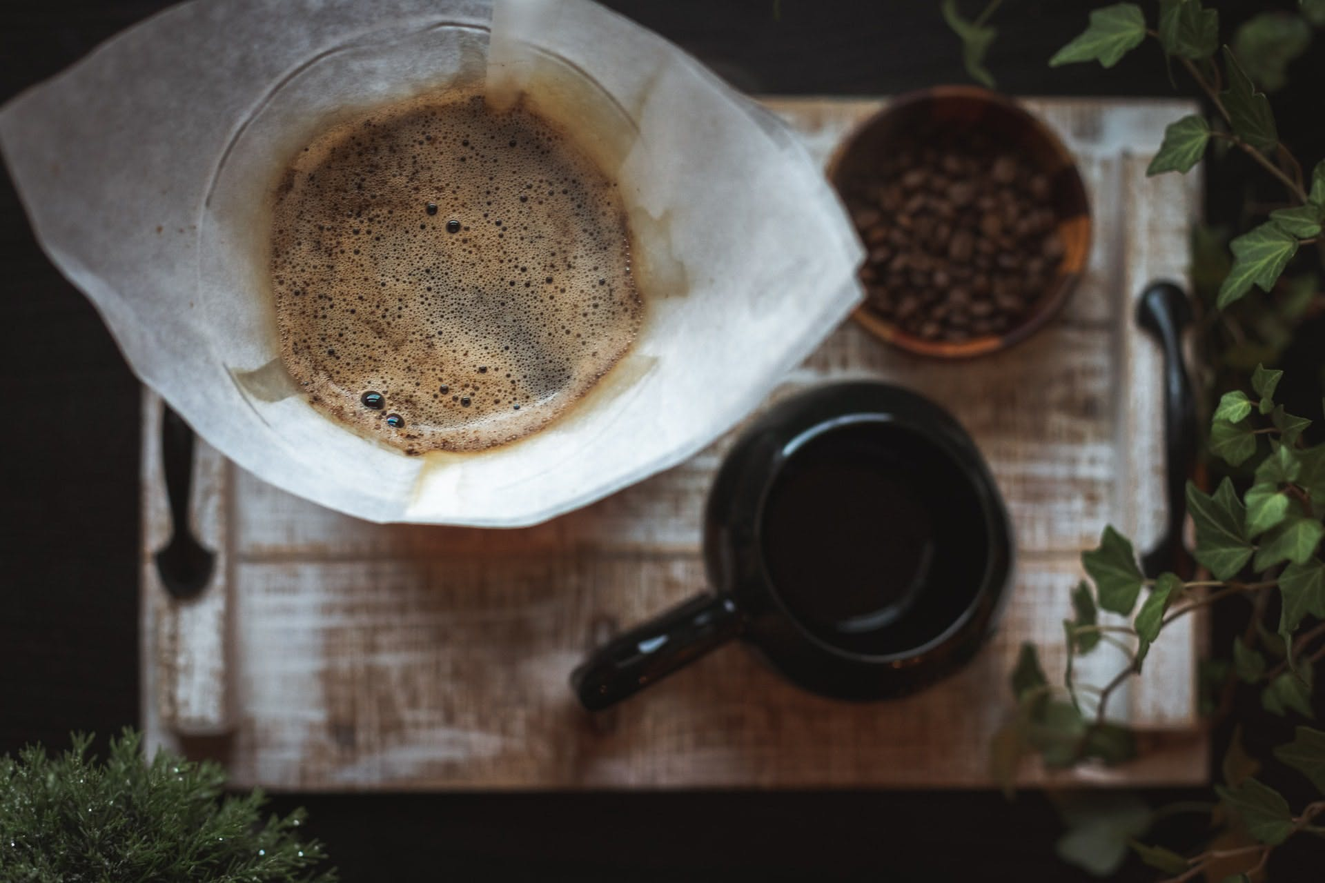 Drip coffee surrounded by a bowl of coffee beans and a black mug.