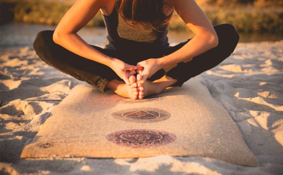 A woman does yoga on a cork mat on a sand beach.