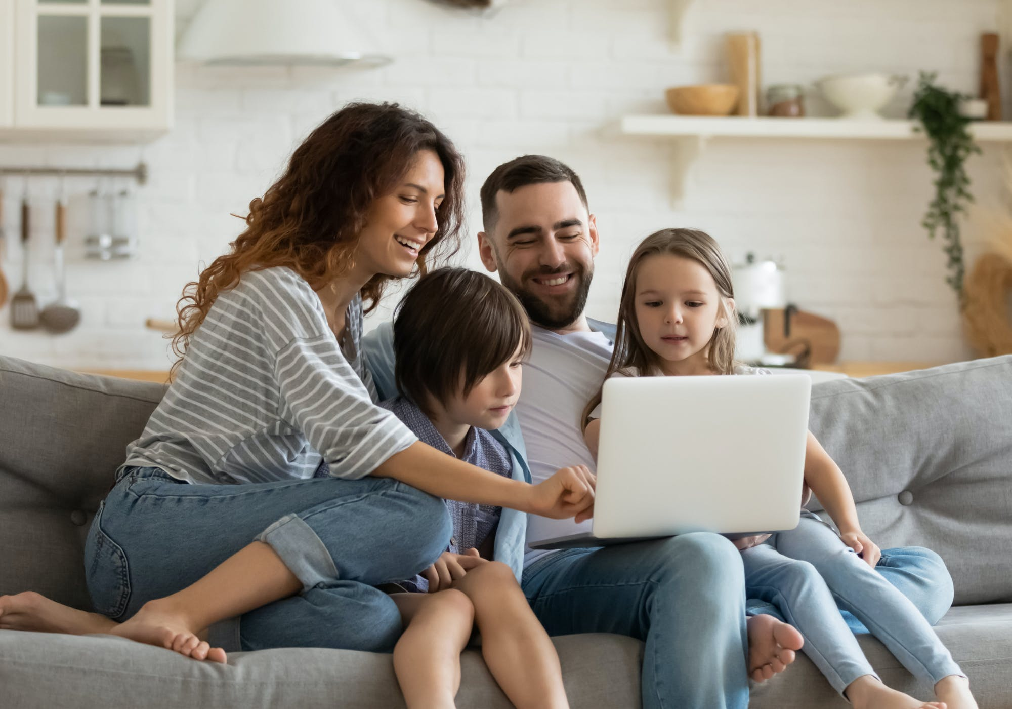 Two parents and their little boy and girl, on a couch, looking at a laptop