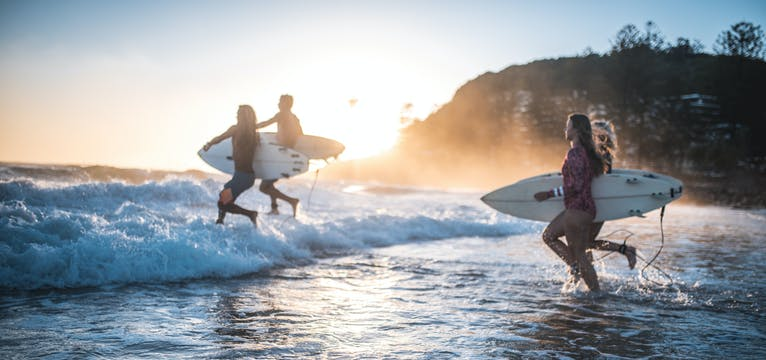 Surfers running into the water on the Gold Coast.