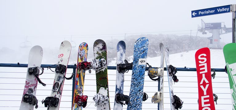Snowboards lined up agains a fence in Perisher Valley, Australia.