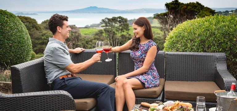 Couple toasting red wine on Waiheke Island, New Zealand.
