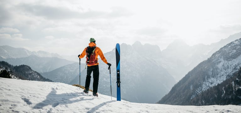 Man standing with skis at the top of a mountain.