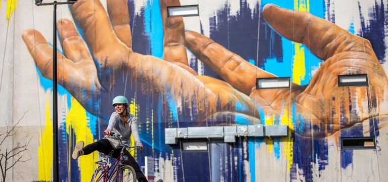 Cyclist in Christchurch in front of graffiti art.