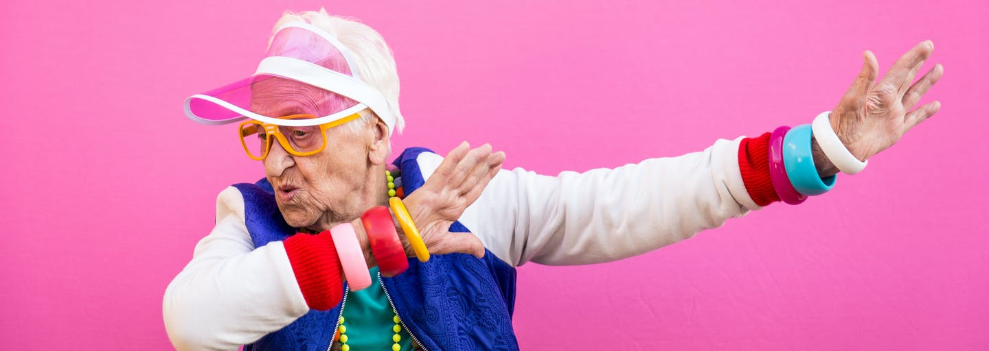 Elderly lady dressed in bright colours and jewellery and a pink hat is dabbing.