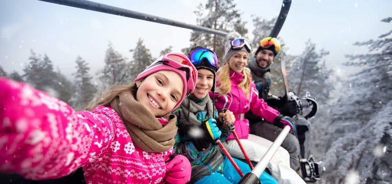 Family on a chairlift above a ski field.