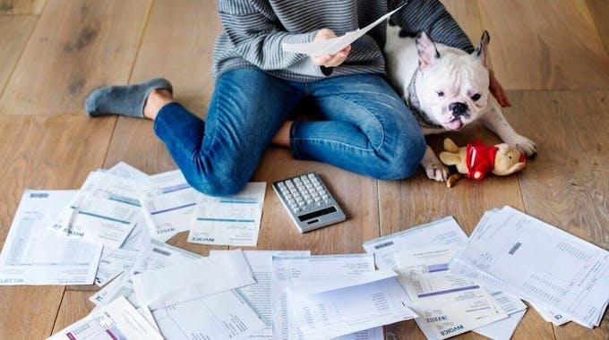 Frau mit Hund sitzt auf dem Boden vor Unterlagen - Schulden
