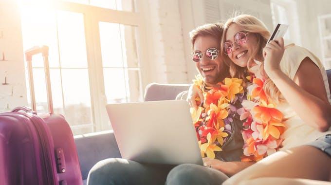 Pärchen bei Urlaubsvorbereitung auf dem Sofa mit Laptop nach Sparpotenzial suchend