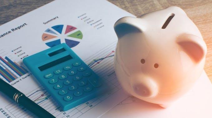 Sparschwein neben Taschenrechner und Bankunterlagen