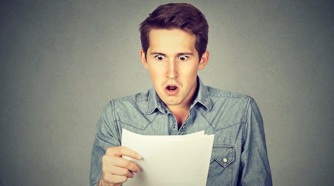 Schockierter Mann mit Dokumenten in der Hand