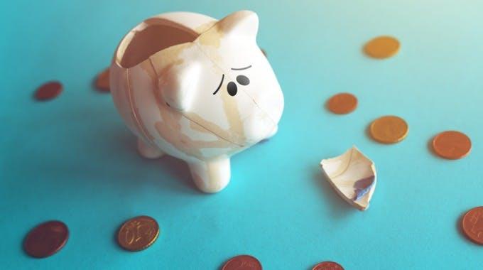 Kaputtes, trauriges Sparschwein mit Euro-Münzen