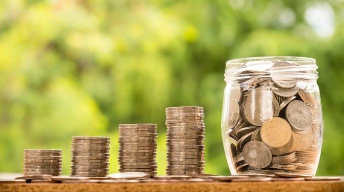 Gestapelte Münzen, aufsteigend, Glas mit vielen Münzen