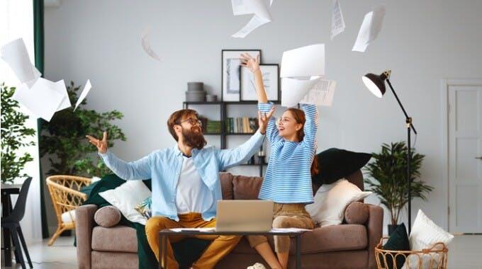 glückliches Ehepaar auf dem Sofa vor Laptop